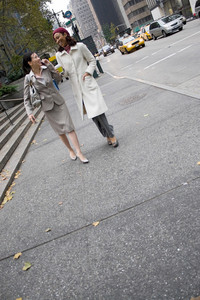Two business women walking in the big city with plenty of copy space. One woman is on her cell phone.