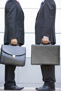 Two businessmen holding briefcases outdoors