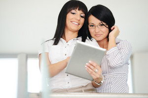Two businesswomen working on tablet gadget with copy space
