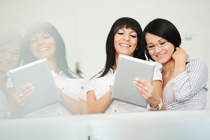 Two businesswomen working on tablet gadget with reflection in glass