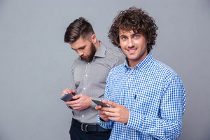 Two casual men using smartphone