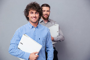 Two cheerful businessmen holding folders