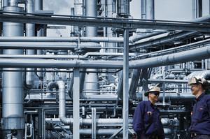 two chemical engineers working inside refinery
