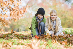 Two children collecting autumn leaves