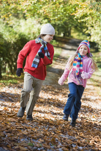 Two children playing in autumn woodland