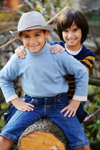 Two children portrait on timber tree outdoor in nature