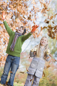 Two children throwing autumn leaves in the air