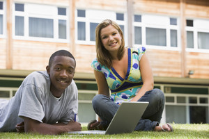 Two college students using laptop on campus lawn,
