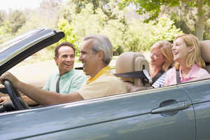 Two couples in convertible car smiling
