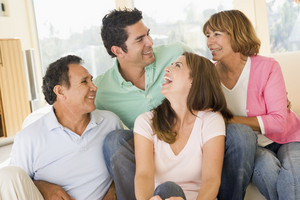 Two couples sitting in living room smiling and laughing