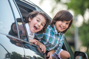 Two cute smiling kids looking out from car window
