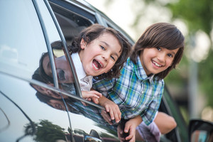 Two cute smiling kids looking through car window