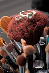 Two diamond rings resting upon some makeup brushes.  One is a diamond engagement ring and the other is a wedding band. Shallow depth of field.