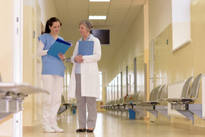 Two female doctors standing in empty hospital corridor