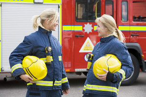 Two female firefighters by a fire engine