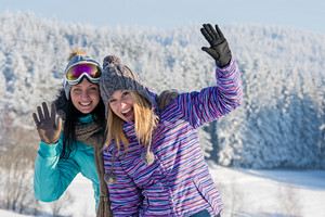 Two female friends enjoy winter snow in mountains holiday break