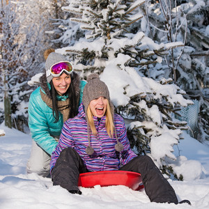 Two female friends on bobsleigh winter snow laughing having fun