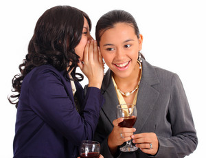 Two Female Officemates Sharing A Secret