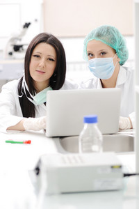 Two female scientists working at the laboratory with laptop