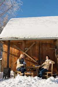 Two girlfriends enjoy tea snow winter cottage sunny countryside