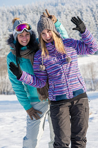Two girlfriends in winter snow mountains smiling and waving on camera