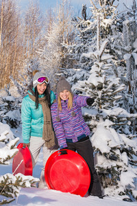 Two girlfriends in winter snowy forest with bobsleigh pointing