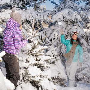 Two girlfriends throw snow balls winter forest enjoy holiday break