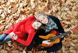 Two girls playing guitar and having good time in nature