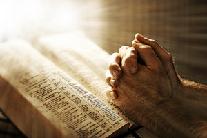 Two hands are in prayer while resting on the Bible