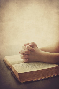 Two hands are on a Bible in prayer