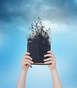 Two hands holding up a Bible that is melting away