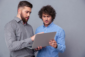Two handsome men using laptop