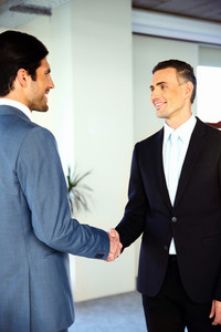 Two happy businessman shaking hands while standing in a hall