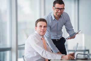 Two happy businessmen posing in office