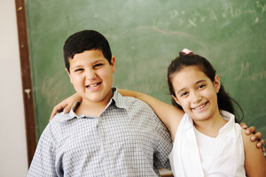Two happy friends in front of green classroom board, school activities