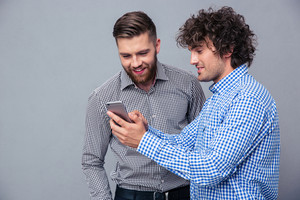 Two happy men using smartphone