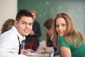 Two happy students sitting in a classroom