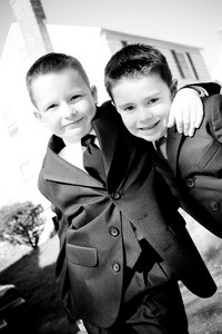 Two happy young boys dressed in suits with smiles on their faces.  Black and white.