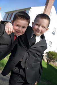 Two happy young boys dressed in suits with smiles on their faces.