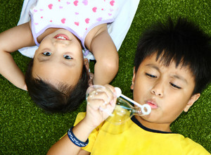 Two Kids Lying And Playing On The Grass