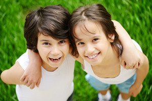 Two little children friends standing on grass and smiling
