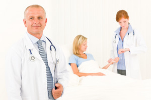 Two medical doctors with patient lying in bed examine pulse