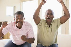 Two men in living room cheering and smiling