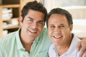 Two men in living room smiling