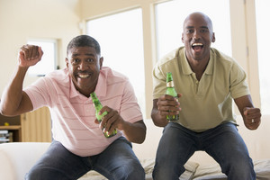 Two men in living room with beer bottles cheering and smiling