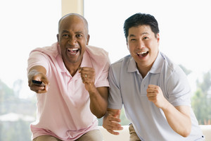 Two men in living room with remote control cheering and smiling