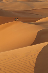 Two photographers atop a sand dune in the desert