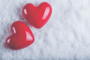 Two red glossy hearts on a frosty white snow winter background