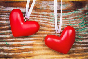 Two red hearts on grunge wooden background