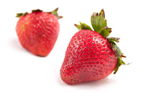 Two red strawberries isolated over white.  Shallow depth of field.